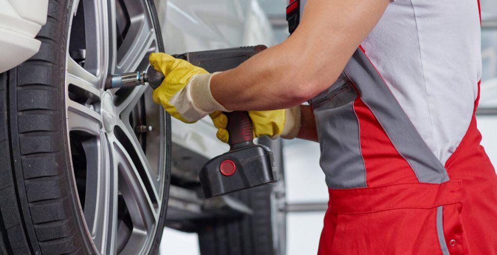 Auto mechanic removing wheel with cordless impact