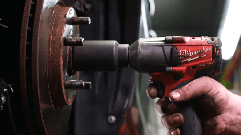 Mechanic using Milwaukee impact wrench to remove spindle nut