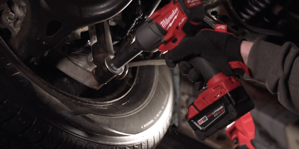 Mechanic using Milwaukee M18 impact wrench to remove suspension bolt