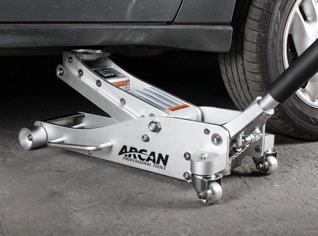 Placing Arcan ALJ3T floor jack under car