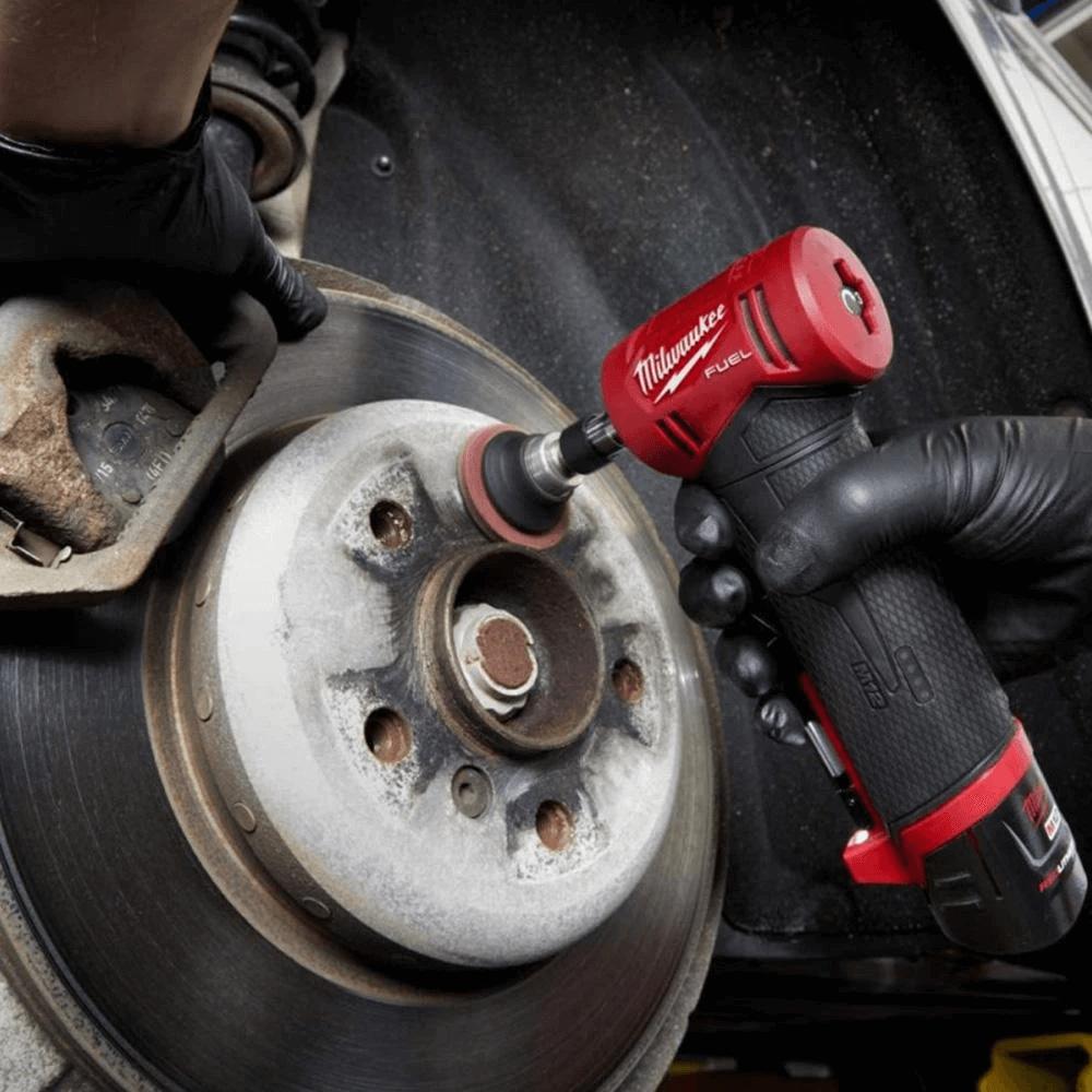 Mechanic using die grinder to clean hub