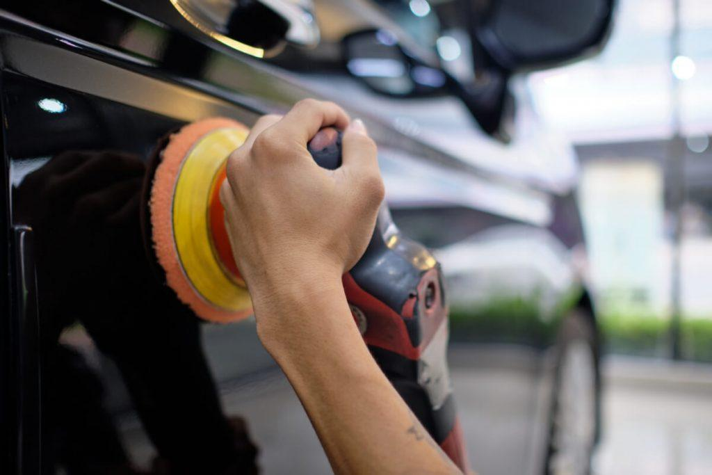 detailing professional buffing a black car