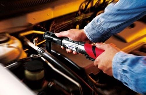Auto mechanic using cordless ratchet wrench