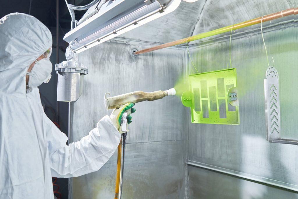 Technician using powder coating system