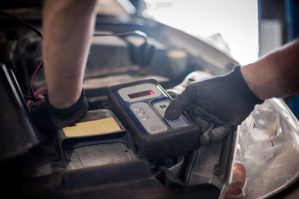 Auto mechanic using battery tester