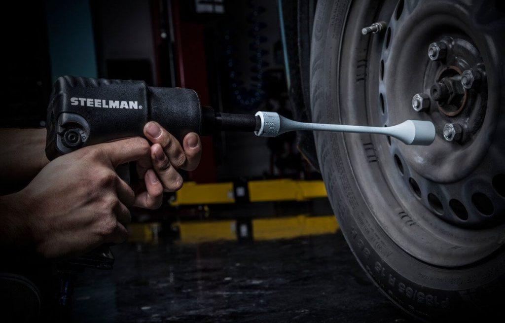 Auto mechanic using torque stick