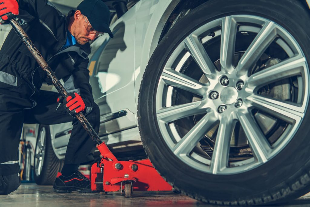 Auto mechanic using 3-ton floor jack