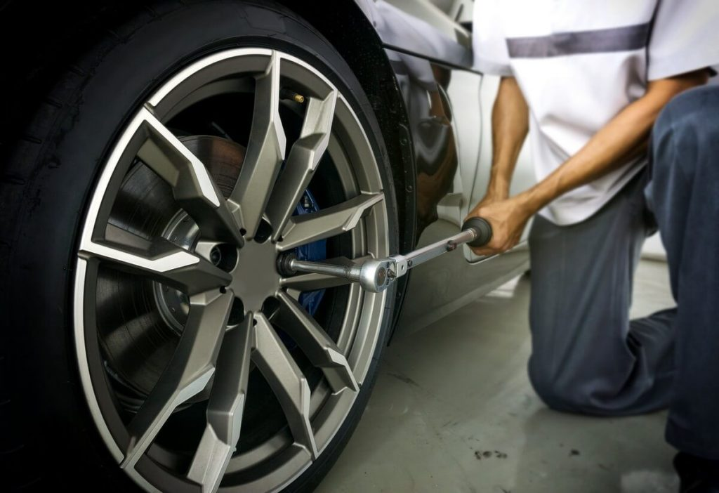 Mechanic tightening wheels using a torque wrench