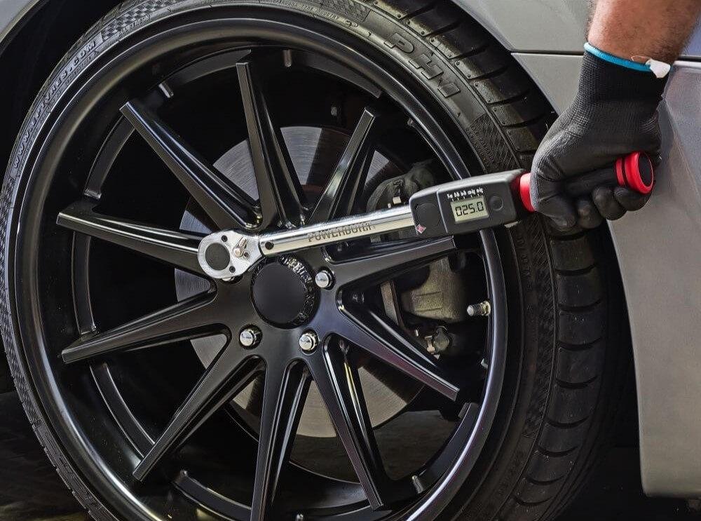 Mechanics using digital torque wrench to torque lug nuts