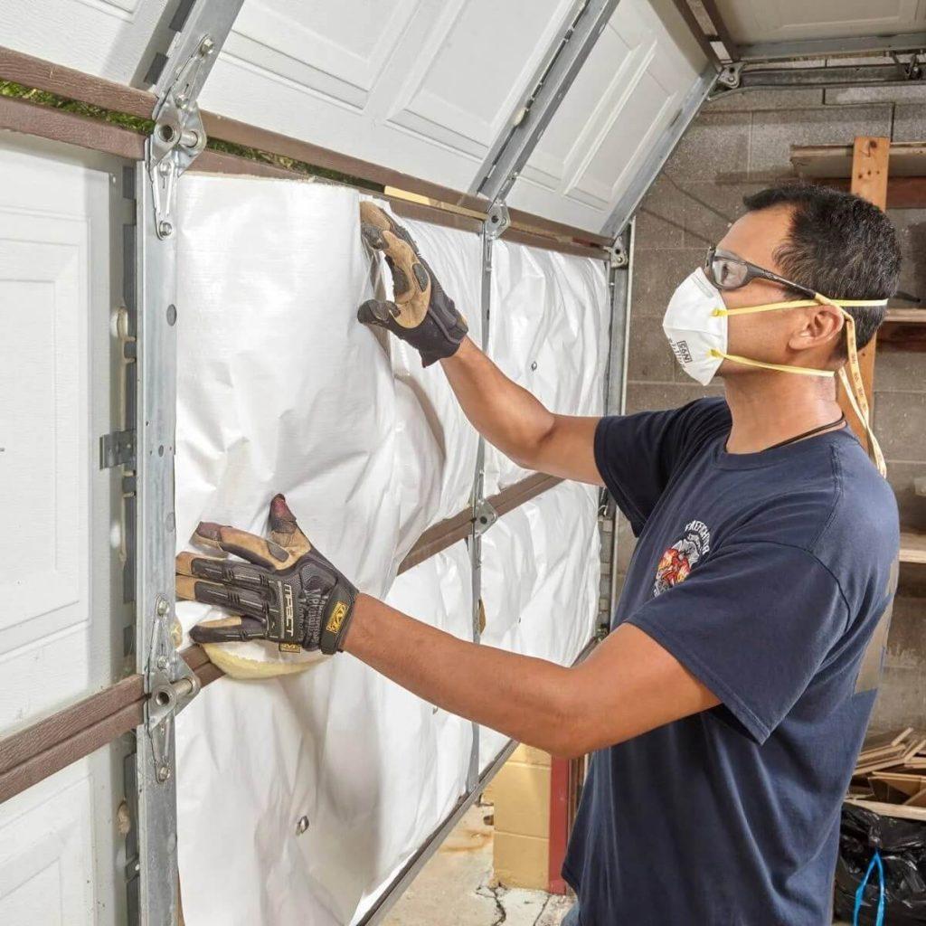 Man installing garage door insulation
